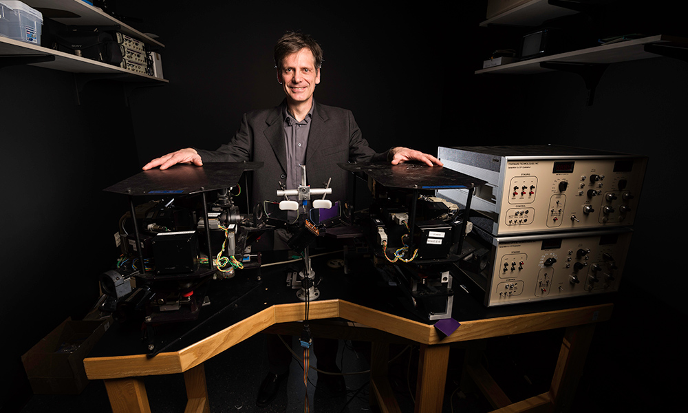Michele Rucci in the lab surrounding by equipment