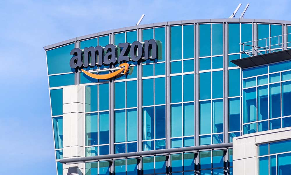 exterior of tall, glass building with the Amazon logo on the side representing Amazon HQ2 finalists