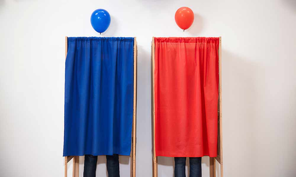 two voting booths, with curtains drawn, one red and one blue, with a blue and red balloon over each
