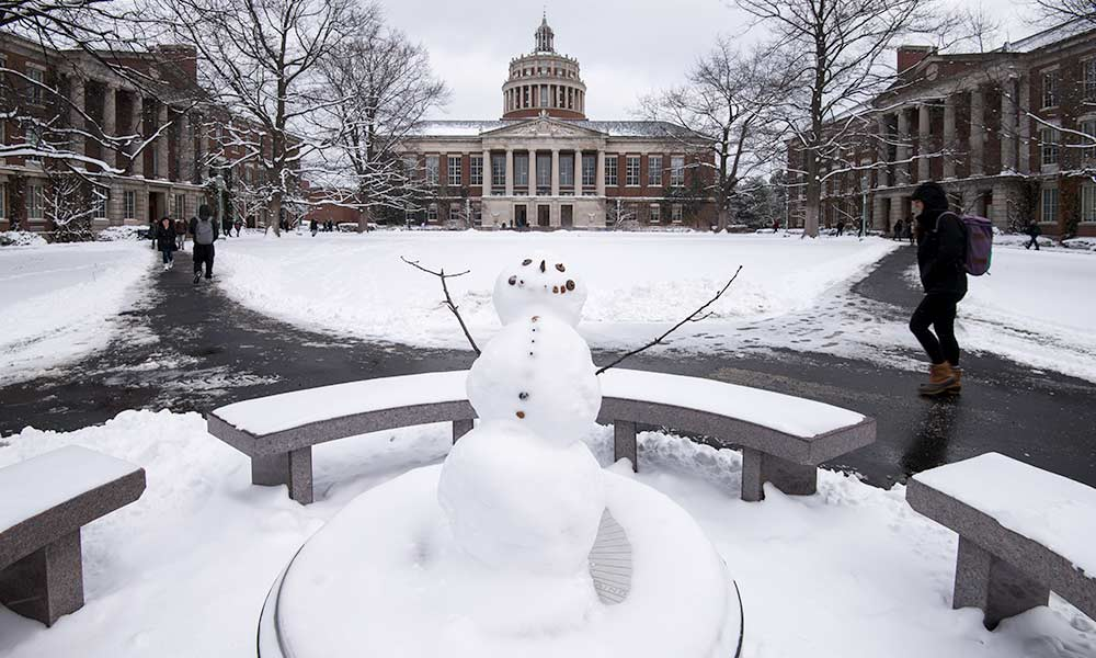 small snowman on the quad as students walk past