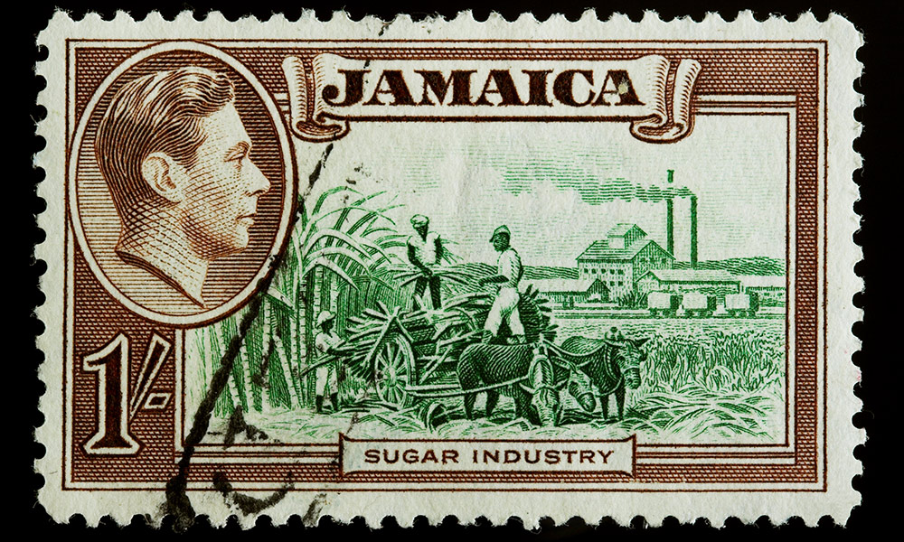 old stamp from Jamaica includes a photo of King George VI and tow black men working a sugar plantation above the words SUGAR INDUSTRY