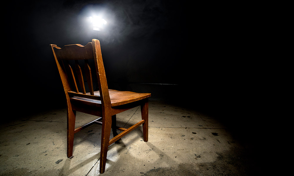 a chair in an empty room with a light overhead, like in an interrogation room