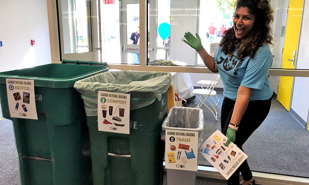 student in a GO GREEN t-shirt poses next to containers for different types of recycling -- recycle, compost, trash