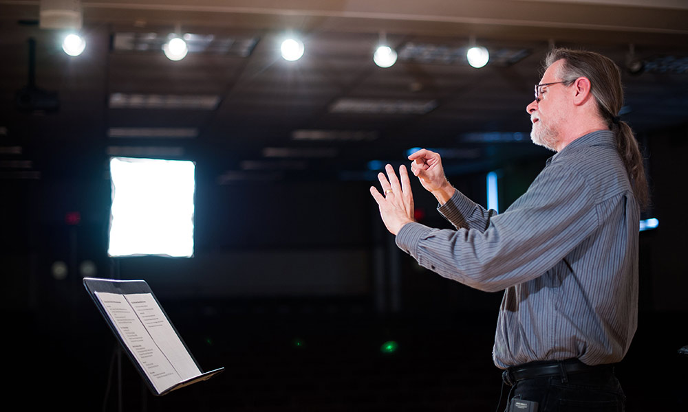 John Covach stands in front of a music stand, conducting