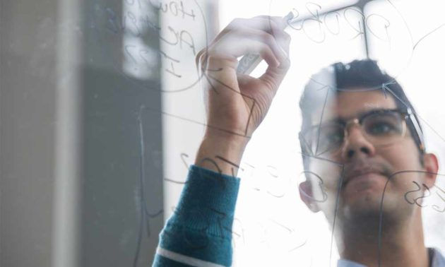 man writing equations on a transparent writing board