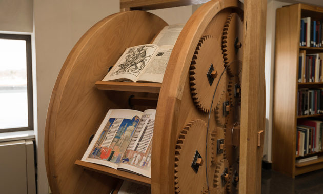 a large wooden wheel holds multiple book shelves and rotates on a series of gears.