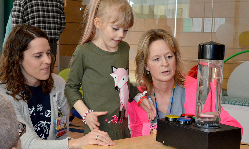 child in the middle, plays with a bubble toy with two adults
