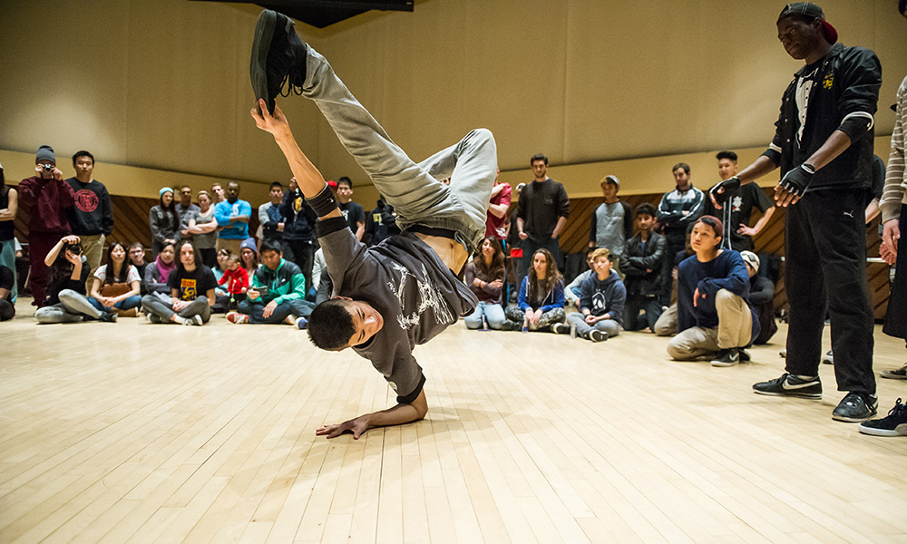 breakdancer performs a move where he grabs his foot with one hand while standing on the other hand.