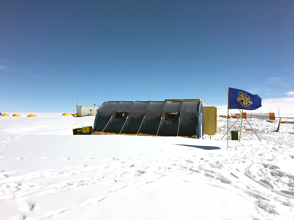 A blue tent sits on a field of ice and snow, with a University of Rochester MELIORA flag flying in front.