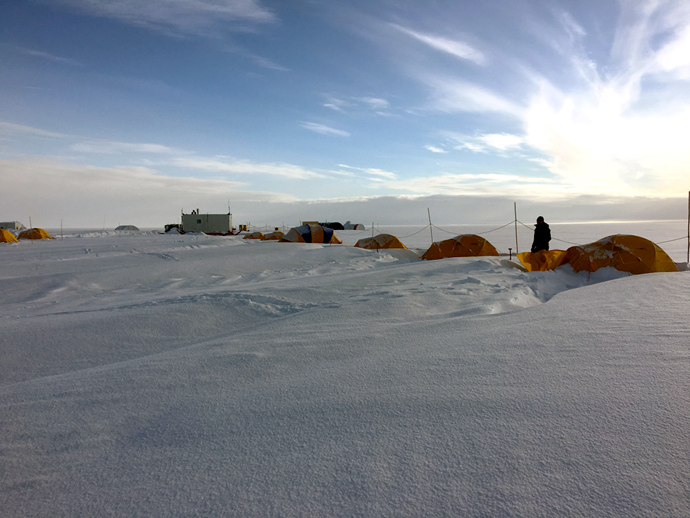sunset over a camp of tents on a vast field of ice and snow.