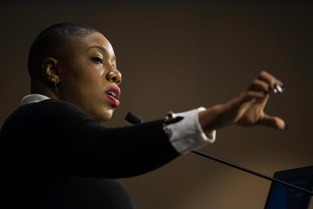 Symone Sanders gesturing from behind the podium.
