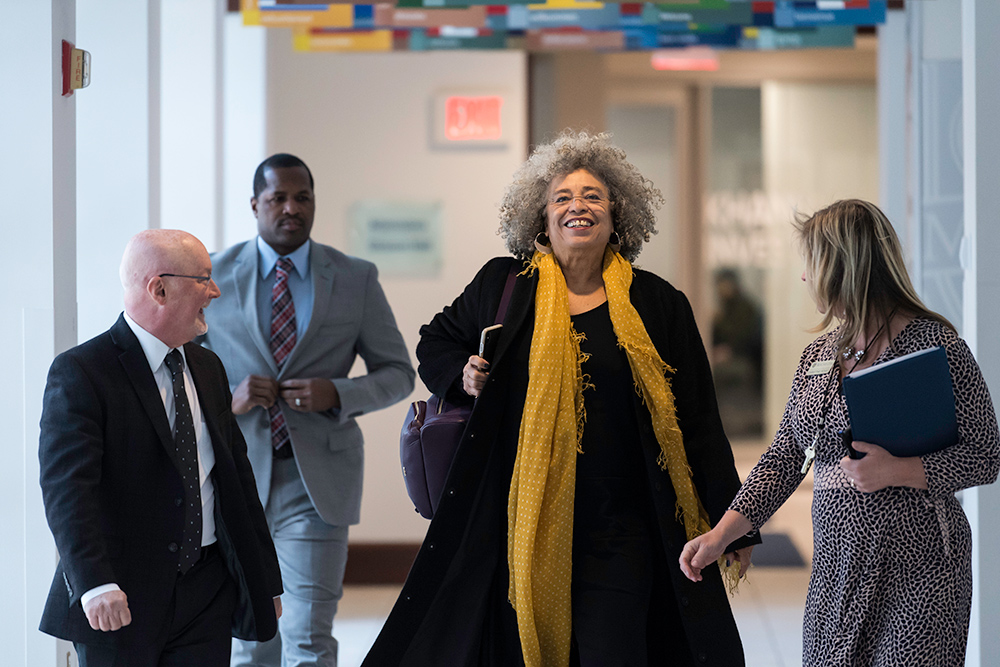 Angela Davis smiling and talking as she walks down a hallway with University administrators and staff.