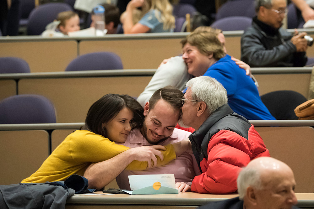 student holds and envelope while people on either side of him kiss and hug him.