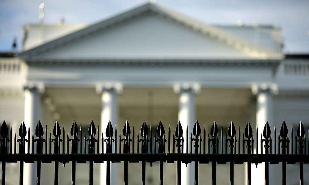 the White House in the background, with a metal fence in the foreground, signalling the idea of a divide.