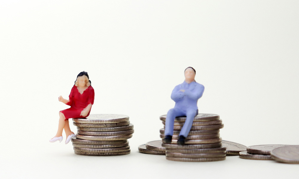 two figures of a man and a woman, each sitting on a pile of coins, to symbolize lack of equal pay for women.