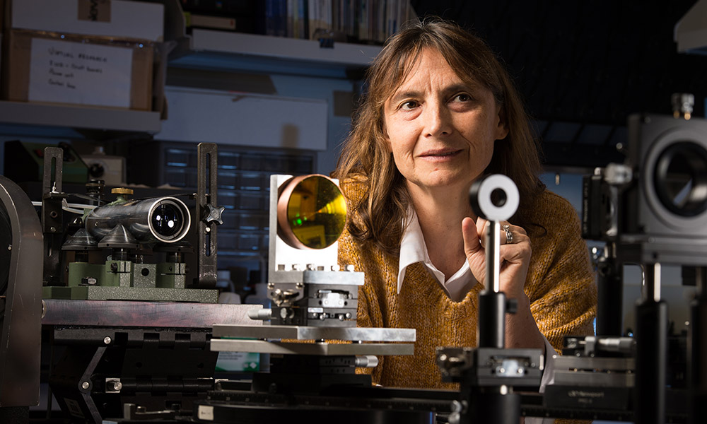 Jannick Rolland in her lab surrounded by lenses and other optical equipment.