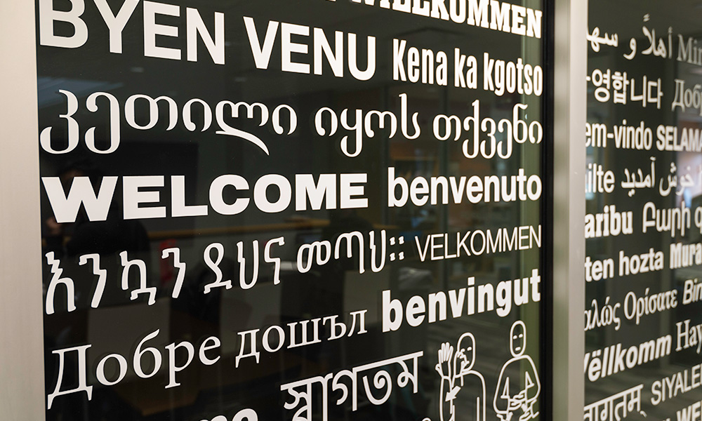 close-up of window of Language Center, covered in greetings in multiple languages.