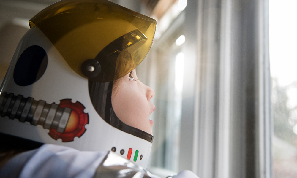 child wearing an astronaut helmet gazes out the window.