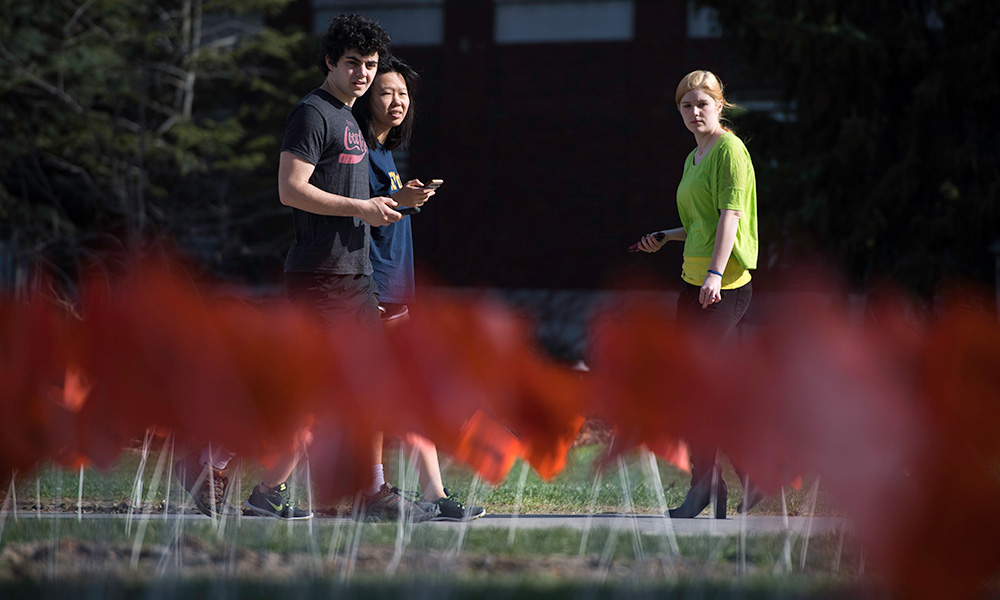 students walking past a large sea of small red flags planted in the ground in front of Wilson Commons.