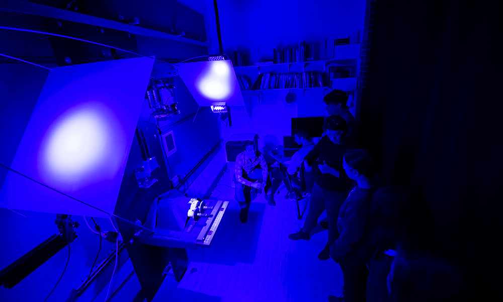 students and professors in a crowded lab, flooded with blue light