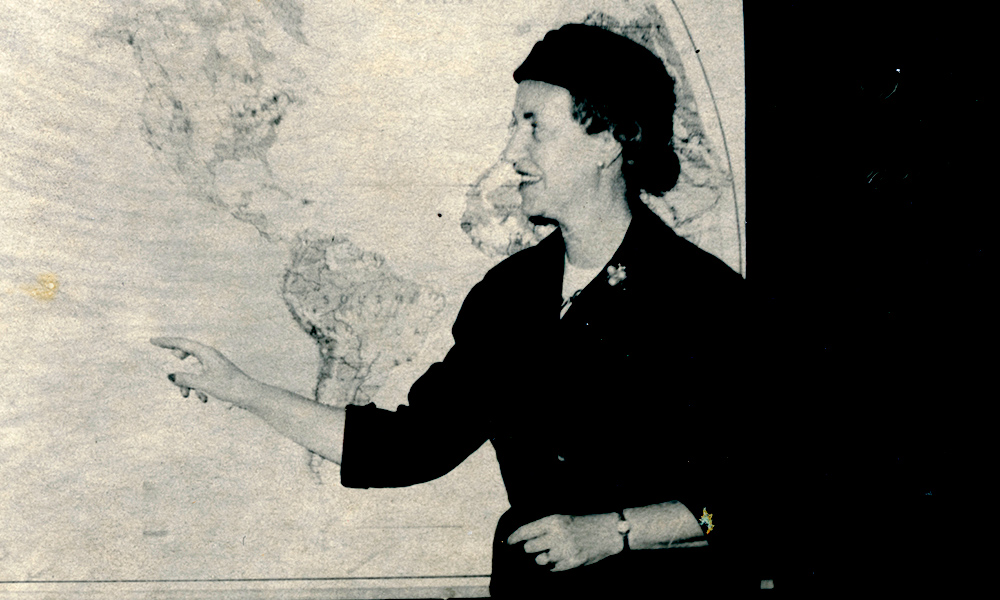 archival image of Vera Micheles Dean teaching in front of a world map.