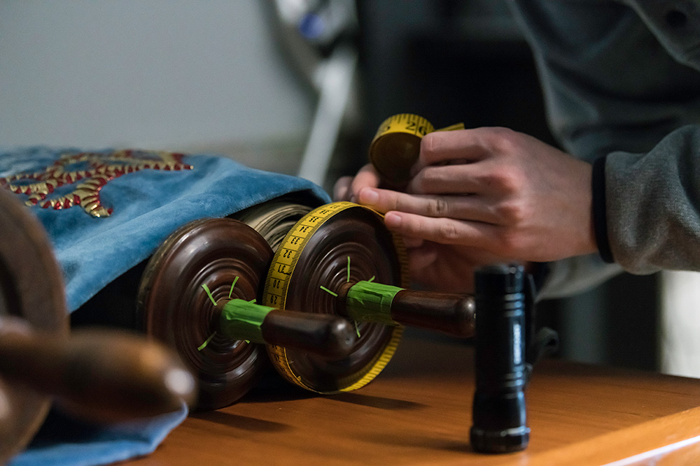 closeup of a torah scroll, with hands holding a tape measure around its edge