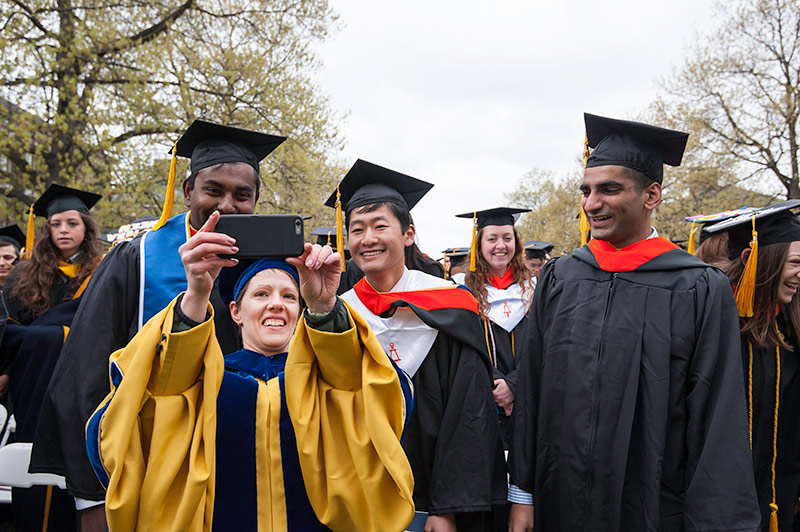 professor taking a selfie with four graduating students, all dressed in caps and gowns.