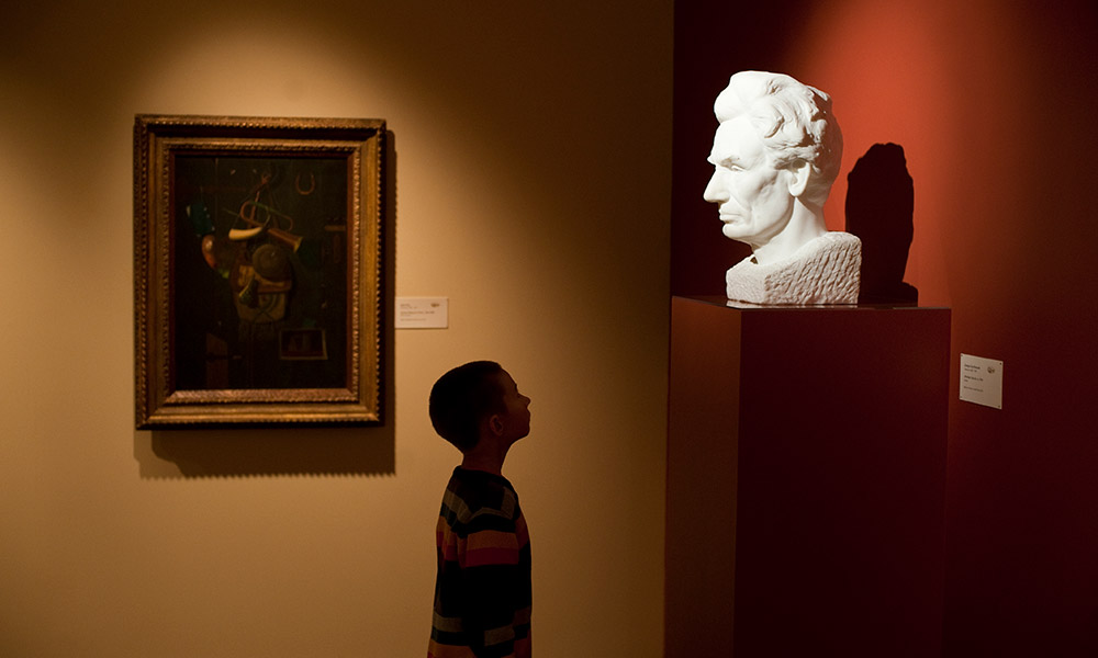 child looks at marble bust of Abraham Lincoln in a museum.