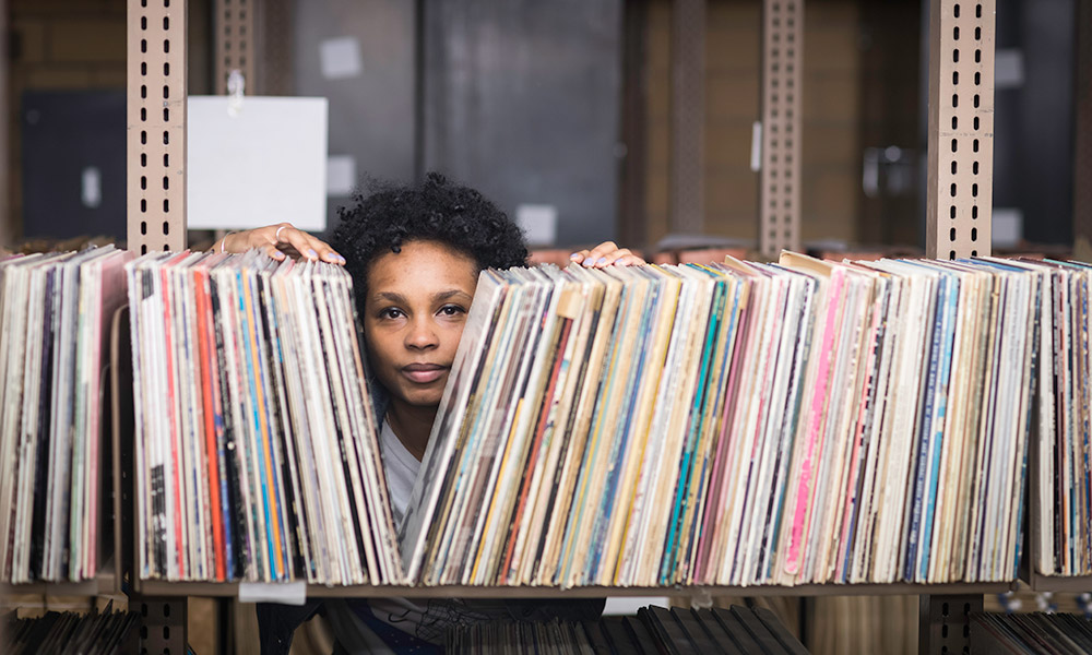 artist Ash Arder stands in a music library, looking through a long shelf filled with record albums