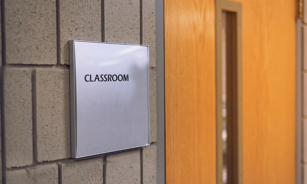 a sign reads CLASSROOM outside a door, symbolizing the tensions between open freedom of speech in higher education and the safety and inclusivity often embodied in trigger warnings in classroom material.