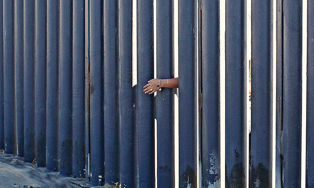 person's single hand reaching through a border fence.