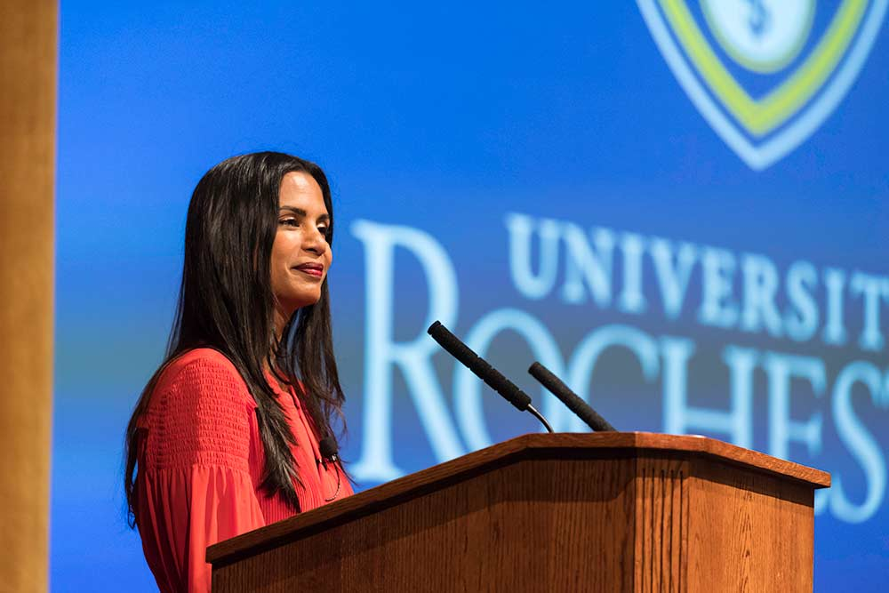 Speaker stands at a podium on a stage, with the University of Rochester logo projected behind her.