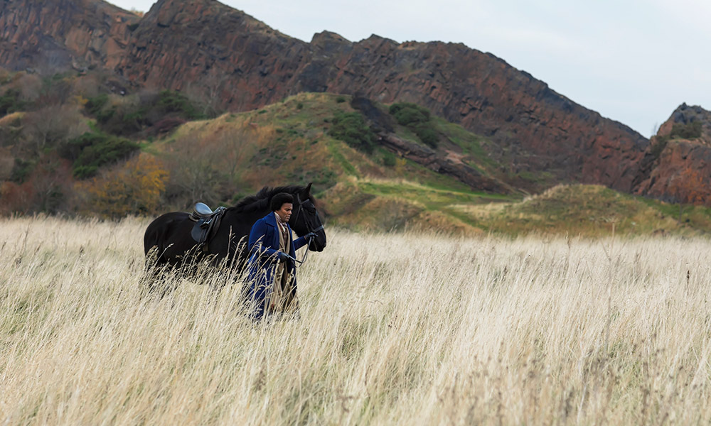 video still of an actor playing Frederick Douglass, walking a horse through a field