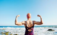 older woman in a swimsuit and cap flexing her muscles at the beach.