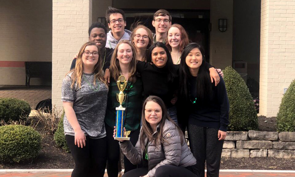 group photo of mock trial team, with one member holding a trophy