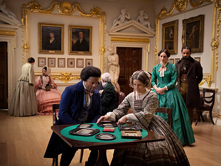 still from a video screen of Lessons of the Hour installation shows actors portraying Frederick Douglass and other guests in a British drawing room