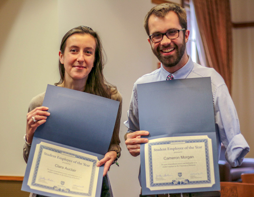 two students holding up certificates of award.
