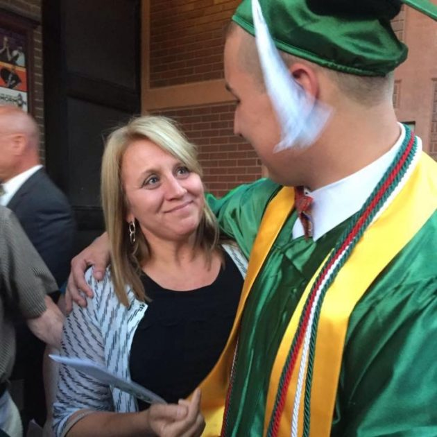 graduate with his arm around his mom