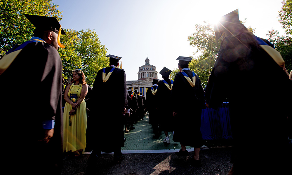 graduates in cap and gown process on the quad toward the library tower.