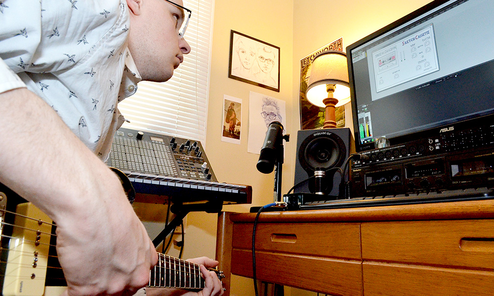 student playing a guitar and looking at a computer screen with the Skethcassette plugin interface on the screen.