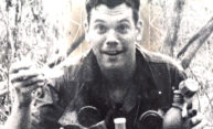 archival photo of soldier smiling, holding a canteen