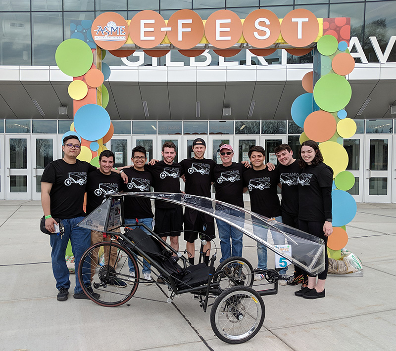 a team of students pose with their human-powered vehicle
