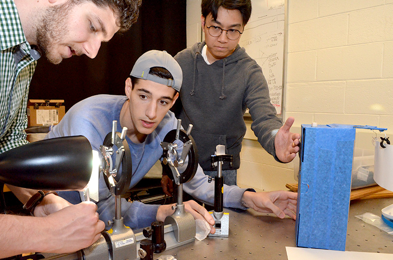 three students working with optics.