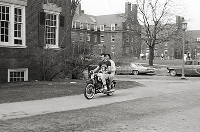 archival photo of two people riding a motorcycle on River Campus