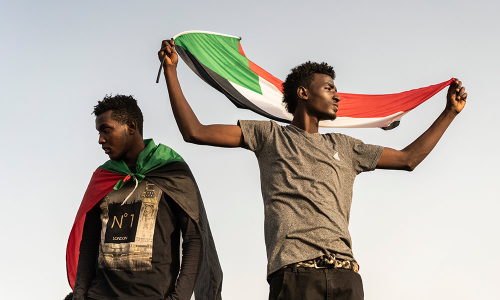 two protesters in Sudan, one holding a Sudanese flag