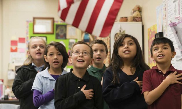 Should patriotism be taught in the classroom? Here, schoolchildren stand for the Pledge of Allegiance.