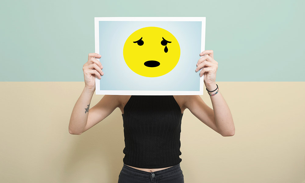 a teenager holds a crying emoticon over their face to symbolize expression of emotions and depression
