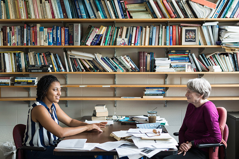 student and professor sit at an office table, the wall behind the filled with bookshelves