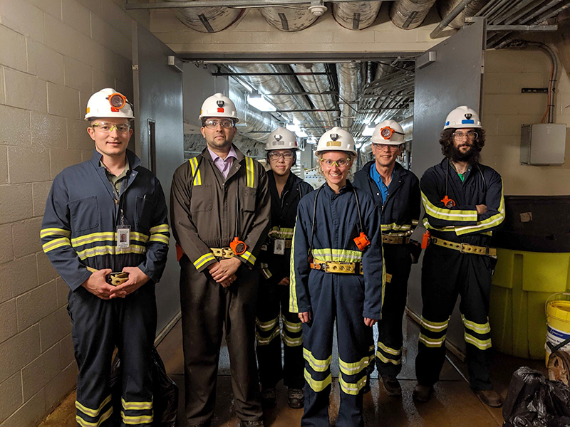group photo of six scientists in hard hats.