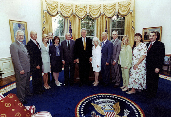 large group of people pose for a photo in the Oval Office, Bill Clinton stands in the center, the presidential seal on the rug.